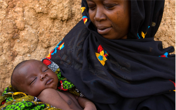 Woman holds a child. © Arne Hoel / World Bank