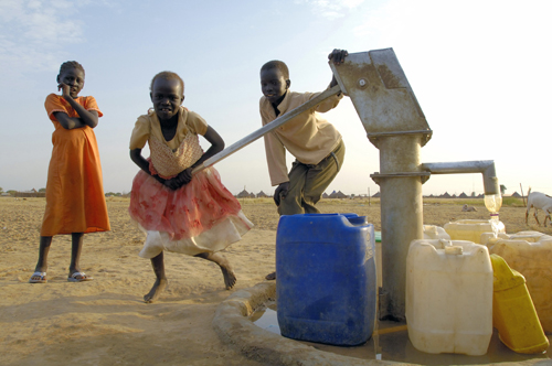Children collect water from a water-pump well in the Abyei suburb of Molomol, where individual voluntary returnees from North Sudan are settling with the assistance of the United Nations. Photo©UN Photo/Fred Noy