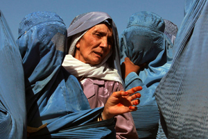 In Herat, Afghanistan, women line up to collect bags of split chick pea, wheat, and cooking oil being distributed by the UN World Food Programme (WFP). © UN Photo/Eric Kanalstein