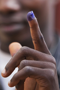 A Liberian holds up his ink-stained finger, proof of his having voted. © UN Photo/Staton Winter